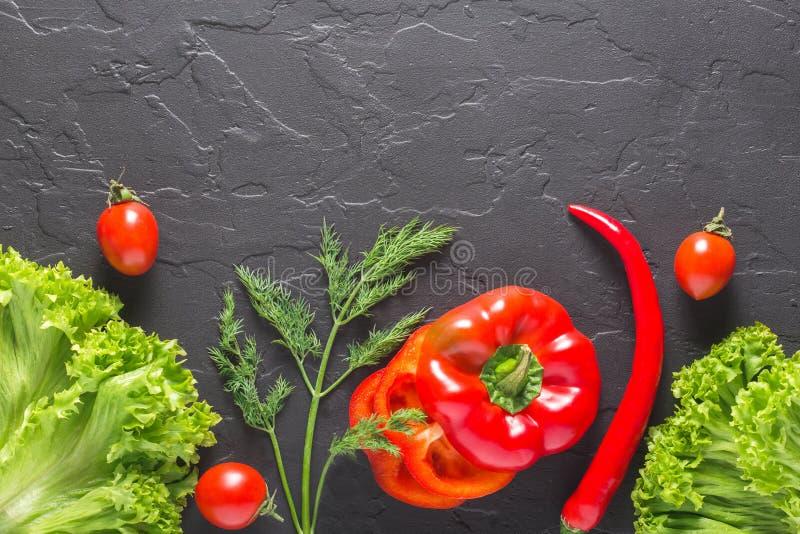 Peterselie, dille, koolbladeren, peper op een donkere concrete achtergrond Verse producten voor salades en vegetarisch voedsel stock afbeeldingen