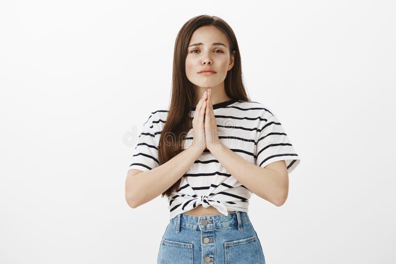 Petición misericordia y disculpa Retrato de la mujer europea joven enfocada preocupante en camiseta rayada, llevando a cabo las m foto de archivo