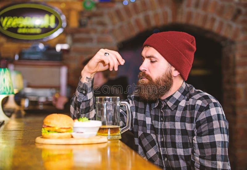Petisco alto da caloria Moderno que relaxa no bar O bar est? relaxando o lugar para ter a bebida e relaxar Homem com cerveja da b foto de stock