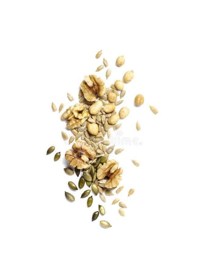 Petisco crocante das porcas, pepitas, sementes de girassol no branco foto de stock