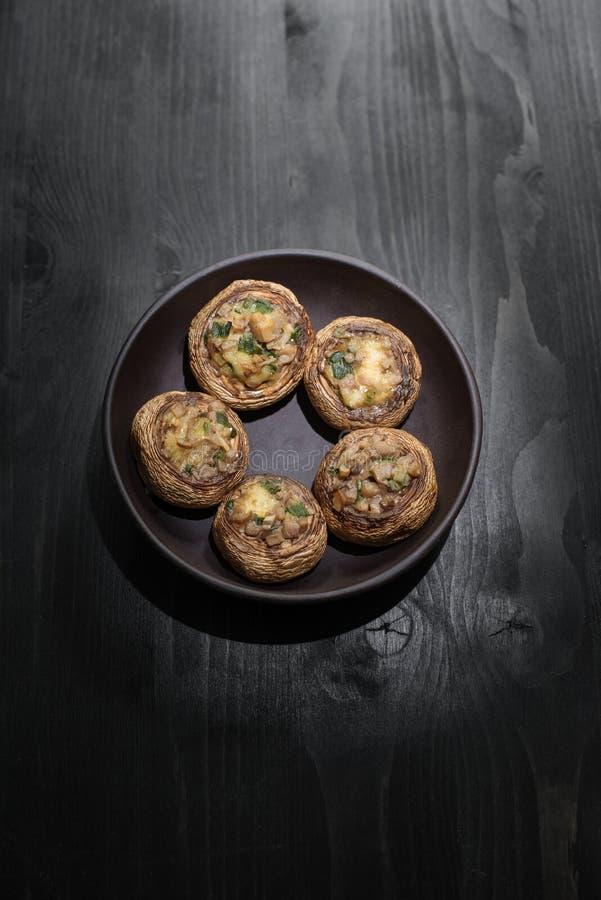 Petisco do cogumelo: queijo cozido nos chapéus Alimento caseiro, cogumelos do círculo da flor em uma placa preta em uma tabela de fotos de stock