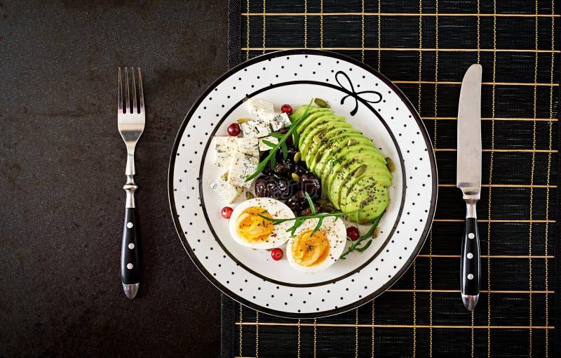 Petisco ou café da manhã saudável - placa do queijo azul, abacate, ovo cozido, azeitonas em um fundo preto Vista superior fotos de stock