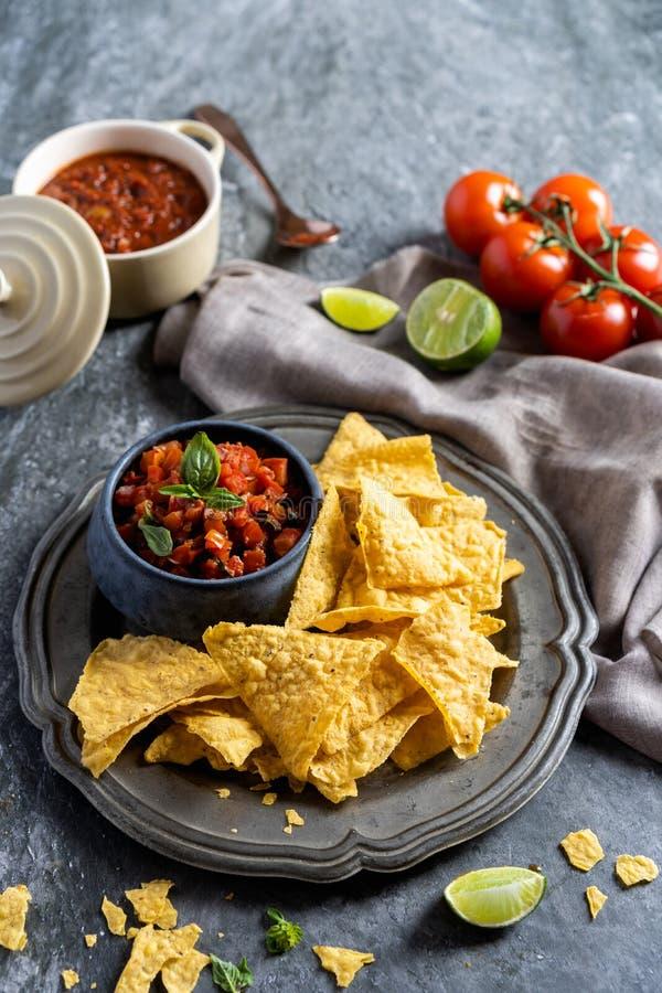 Petisco para um partido, umas microplaquetas de tortilha mexicanas dos nachos do alimento e uma salsa do mergulho com tomate imagem de stock