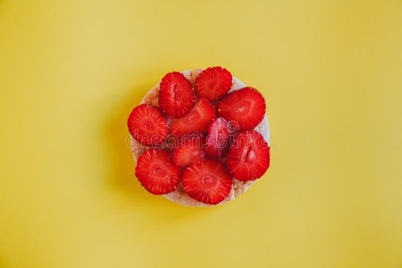 Petisco saboroso e saudável, pão estaladiço com fatias da morango em um fundo amarelo fotografia de stock