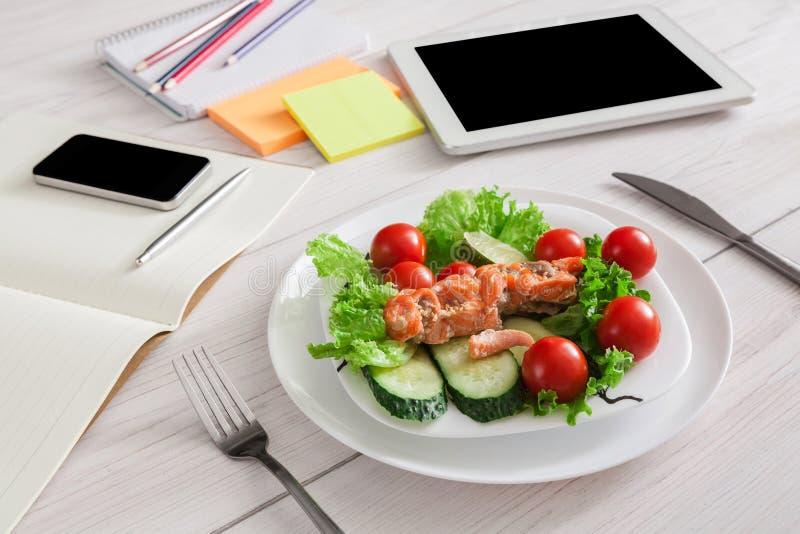 Petisco saudável do almoço de negócio no escritório, salmão com vegetais fotografia de stock