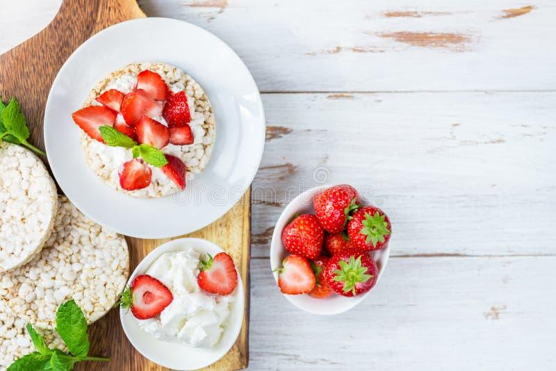 Petisco saudável dos bolos de arroz com ricota e morangos imagem de stock royalty free