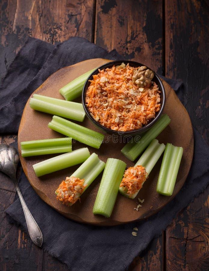 Petisco vegetal delicioso da dieta, hastes do aipo com mergulho da cenoura com porcas, alho, especiarias e molho do iogurte sobre imagens de stock