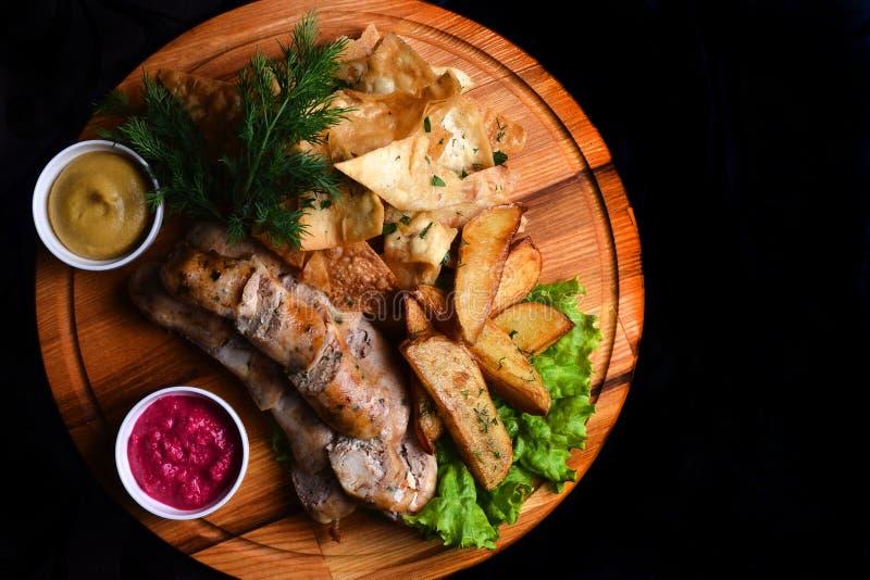 Petiscos à cerveja em uma placa de madeira O Bavarian fritou salsichas, batatas fritadas, microplaquetas isoladas em um fundo pre imagens de stock