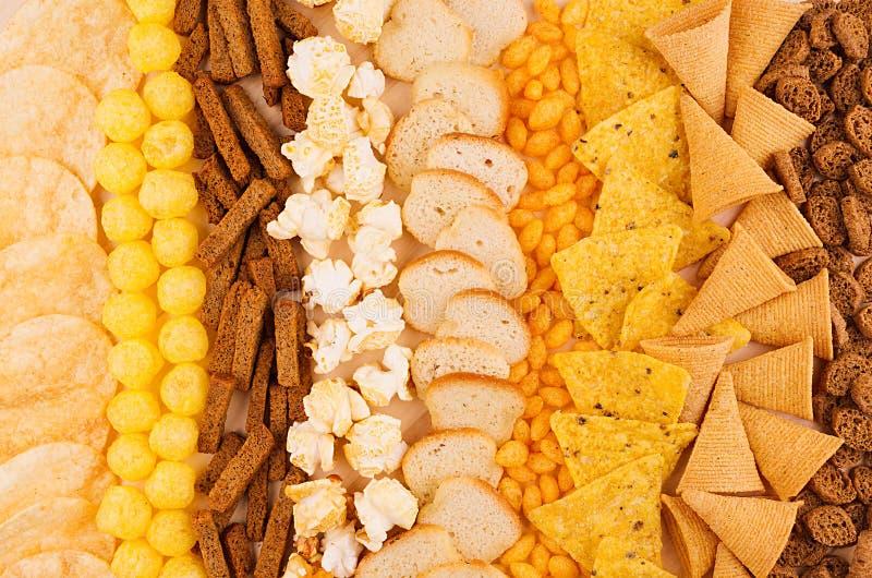 Petiscos crocantes da variedade - a pipoca, nachos, pão torrado, milho cola, microplaquetas de batata como o fundo decorativo, vi fotografia de stock royalty free