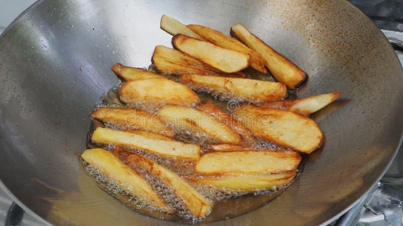 Petiscos da batata de batatas fritas que cozinham com óleo de palma na bandeja foto de stock royalty free