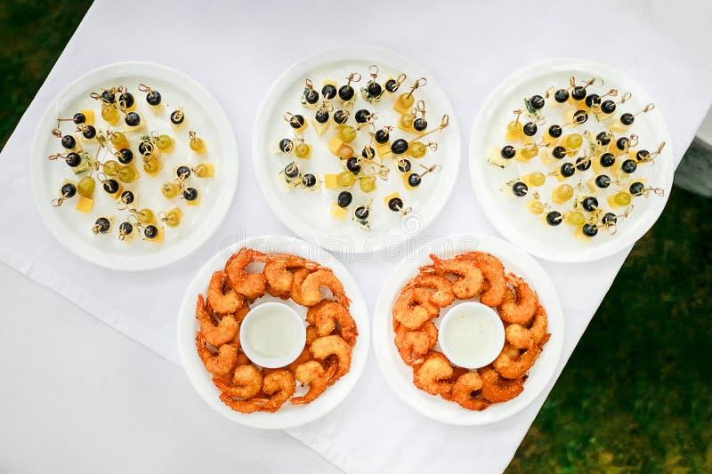 Petiscos da decoração fora, vista superior Camarão fritado do tempura com molho branco, queijo e azeitonas em espetos Cinco placa fotografia de stock royalty free