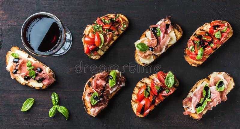 Petiscos de Brushetta para o vinho Variedade de sanduíches pequenos no contexto de madeira rústico escuro imagem de stock royalty free