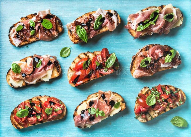 Petiscos de Brushetta para o vinho Variedade de sanduíches pequenos no contexto do azul de turquesa imagens de stock