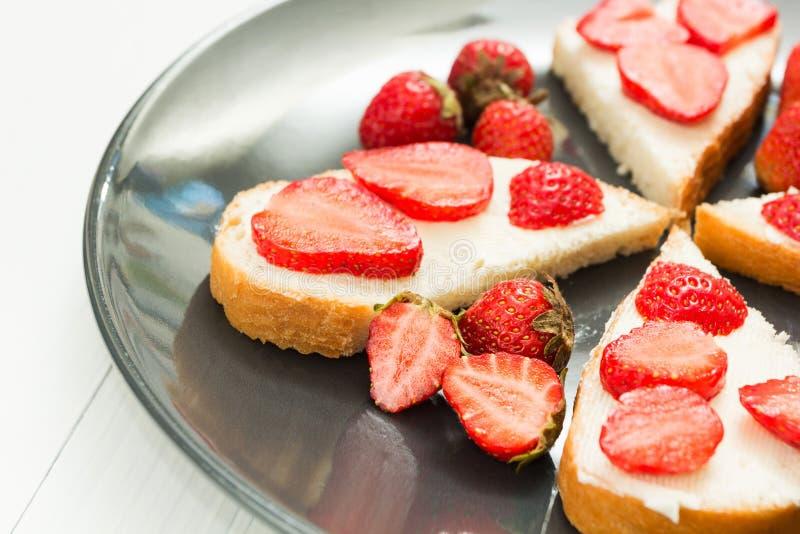 Petiscos de sanduíches frescos com morangos em uma tabela branca imagem de stock