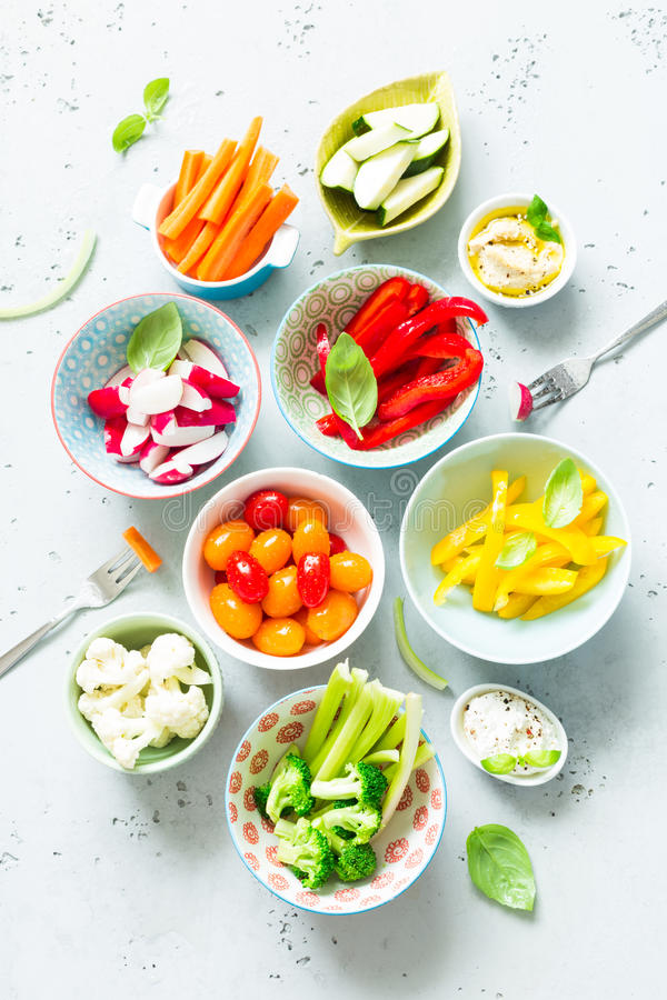Petiscos do vegetariano - vegetais e mergulhos coloridos em umas bacias fotografia de stock