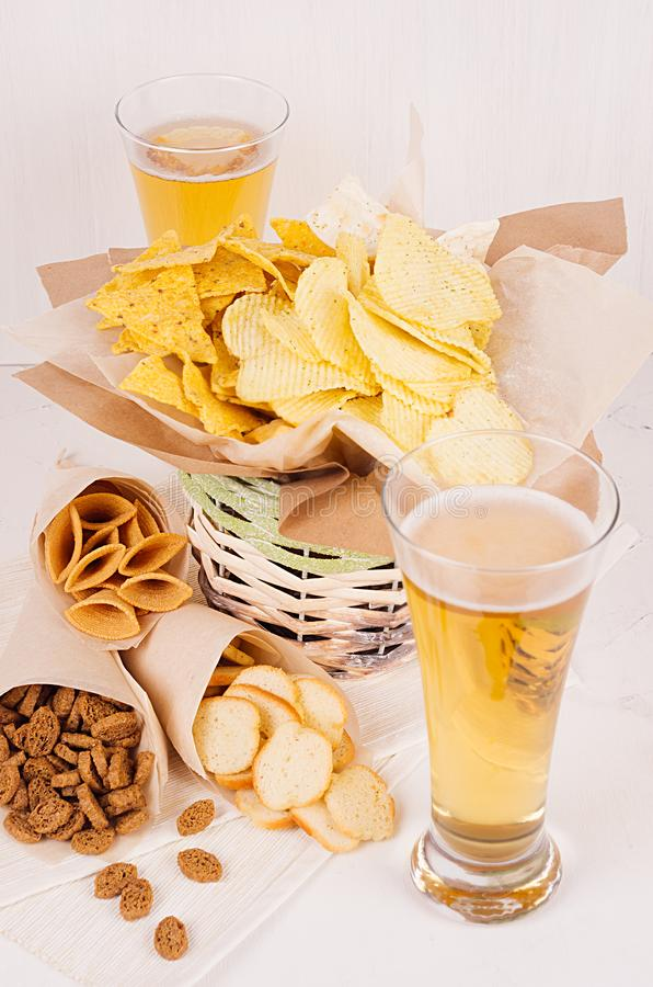 Petiscos do verão e cerveja de cerveja pilsen no vidro - nachos, pão torrado, microplaquetas, tortilha na cesta rústica e cantos  foto de stock royalty free
