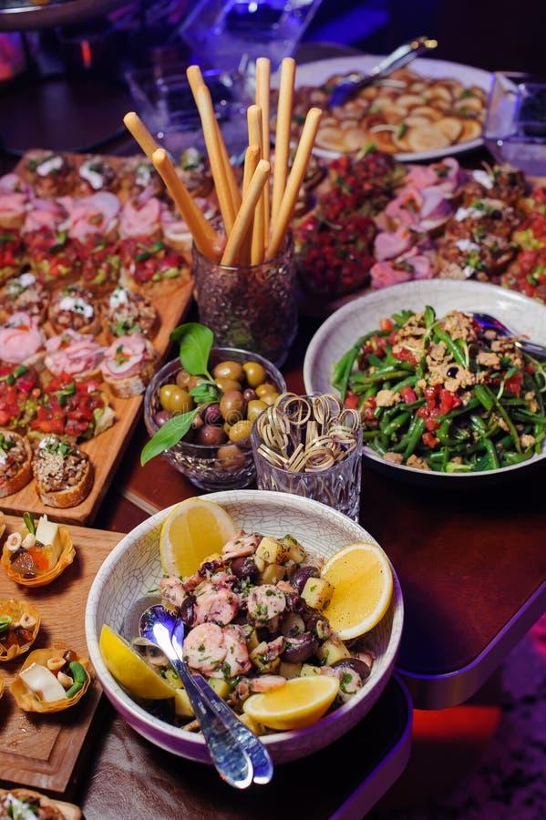 Petiscos e saladas na tabela Foco seletivo imagem de stock