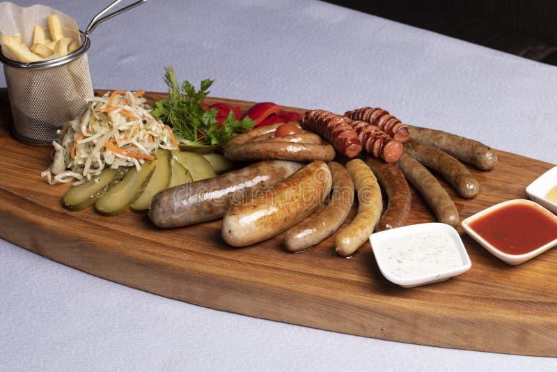 petiscos frios para a cerveja, as salsichas e o queijo com tomates, salsa e a cereja fritados imagem de stock
