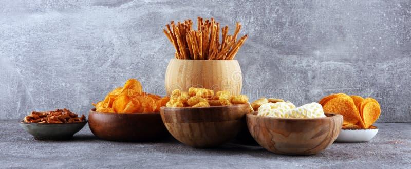 Petiscos salgados Pretzeis, microplaquetas, biscoitos em umas bacias de madeira imagens de stock