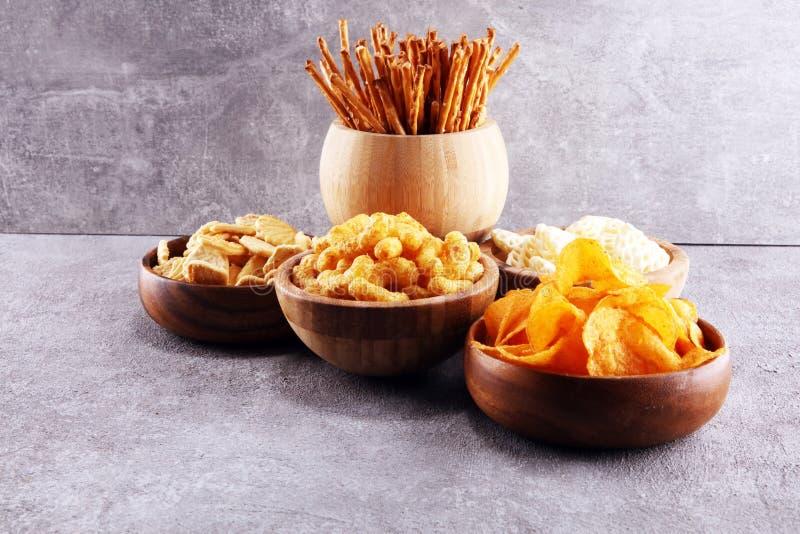 Petiscos salgados Pretzeis, microplaquetas, biscoitos em umas bacias de madeira fotos de stock royalty free