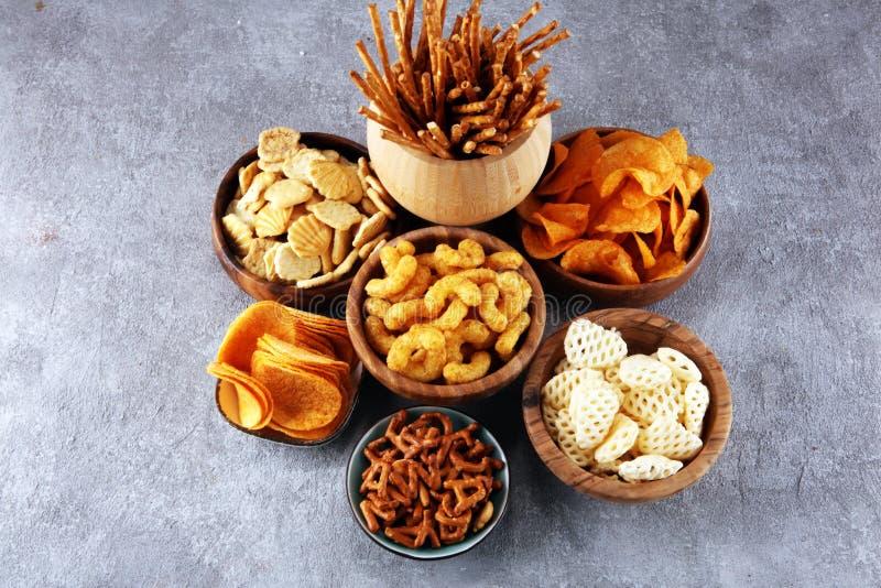 Petiscos salgados Pretzeis, microplaquetas, biscoitos em umas bacias de madeira fotos de stock