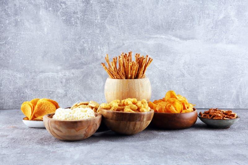 Petiscos salgados Pretzeis, microplaquetas, biscoitos em umas bacias de madeira imagem de stock