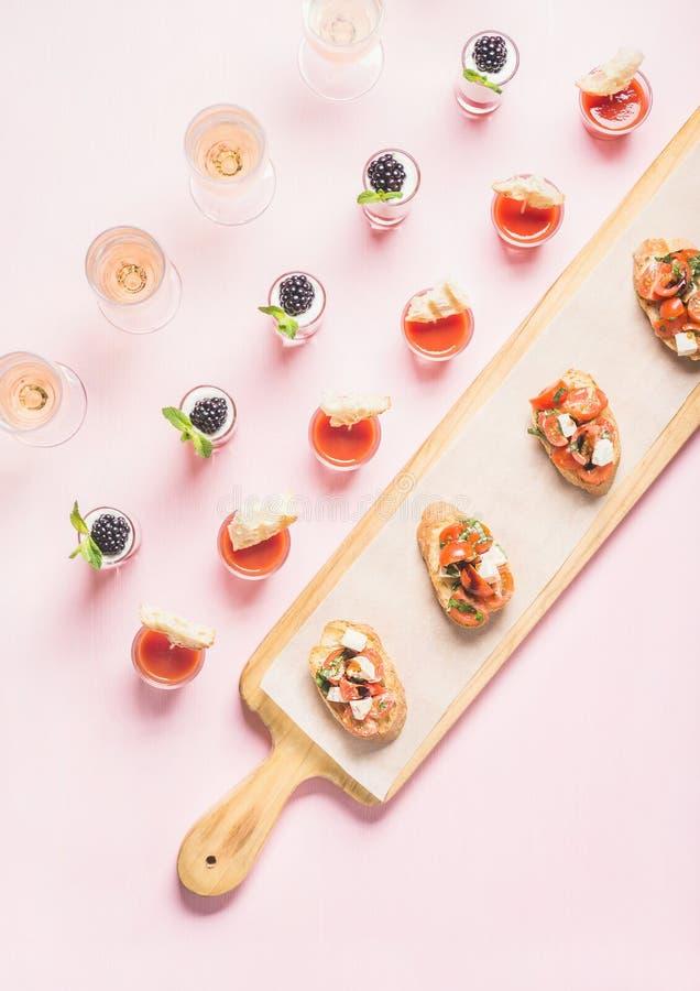 Petiscos, sanduíches do brushetta, tiros do gazpacho, sobremesas sobre o fundo do rosa pastel imagem de stock