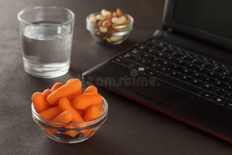 Petiscos saudáveis para o almoço do local de trabalho: cenouras de bebê, amêndoas, caju e vidro da água fotos de stock royalty free