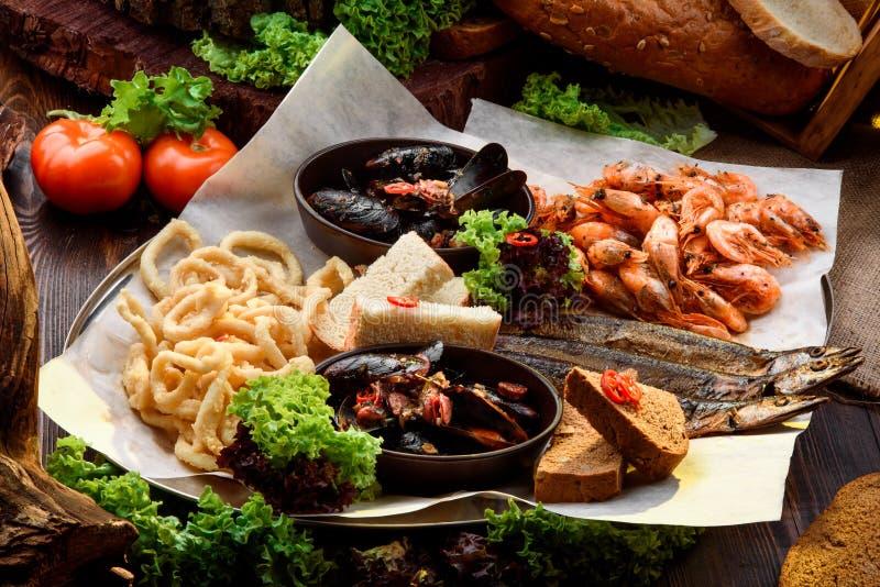 Petiscos sortidos da cerveja: anéis de cebola, peixes fumados, mexilhões e camarões na bandeja no pano de saco entre vegetais foto de stock