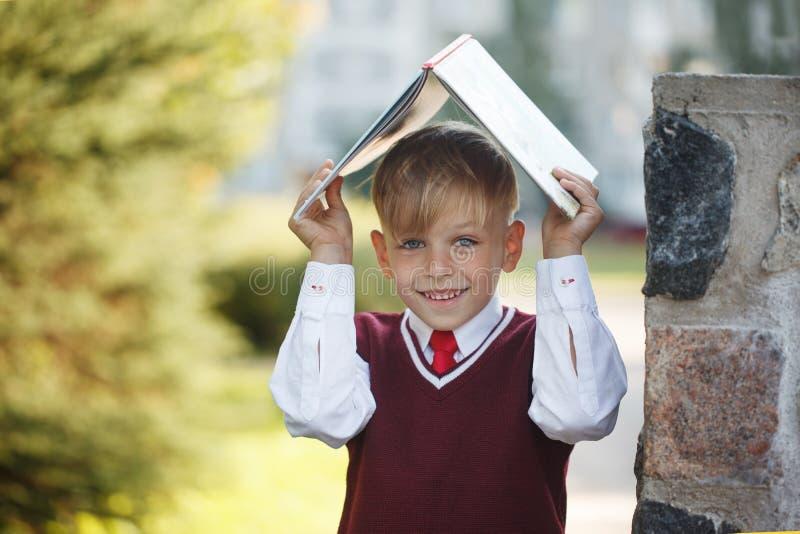 Petit écolier de portrait sur le fond de nature Enfant avec les livres et l'uniforme habillé Éducation pour des enfants De nouvea images libres de droits