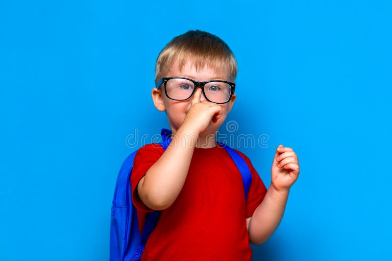Petit écolier de sourire sur le fond bleu dans le toutch en verre ses verres de nouveau à l'école, enfant préscolaire image stock