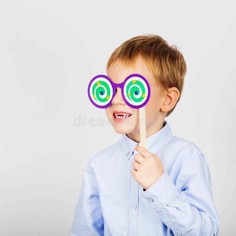 Petit écolier mignon avec des verres de papier drôle contre un blanc photo libre de droits