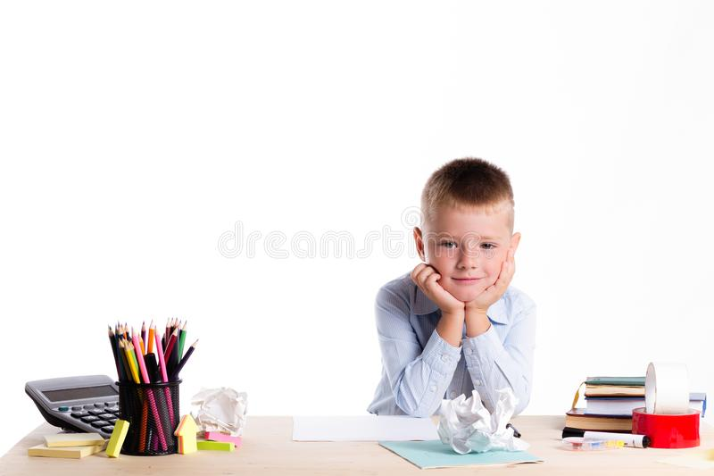 Petit écolier mignon avec le sourire énorme se reposant à son bureau sur le wh photos libres de droits