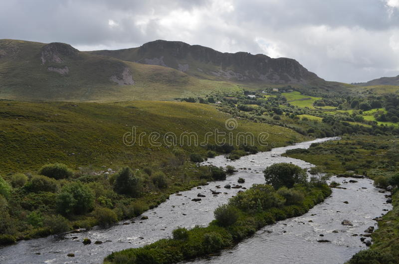 Petit écoulement de rivière dans le paysage vert de végétation et de montagne dans une route nationale en Irlande photos stock