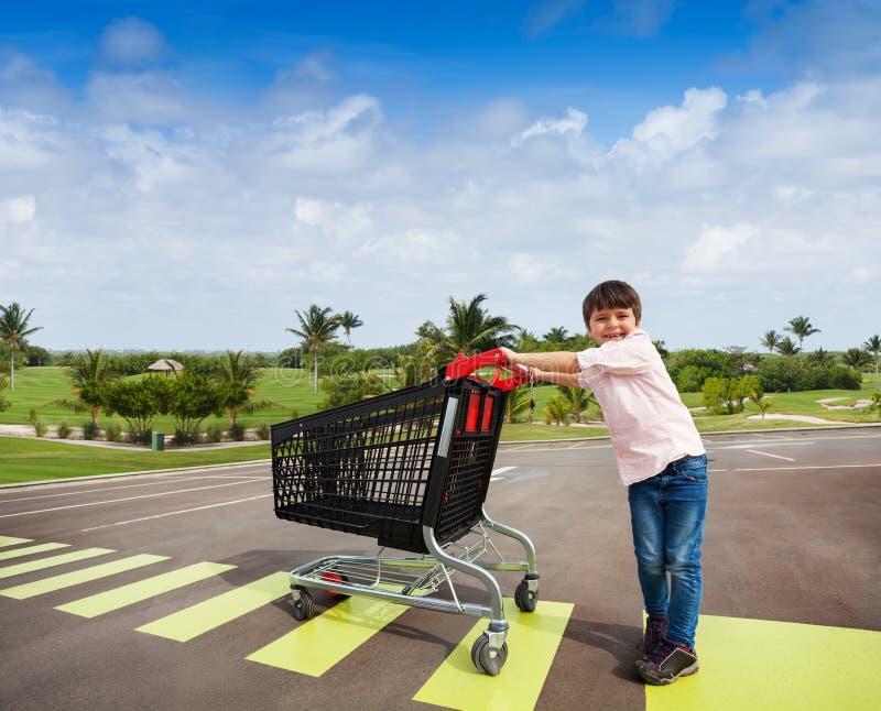 Petit acheteur traversant la route avec le caddie photographie stock libre de droits