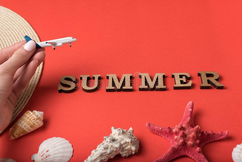 Petit avion dans la main femelle ?t? de Word des lettres en bois Coquillages, étoiles de mer et un fond de corail vivant Concept  photo libre de droits