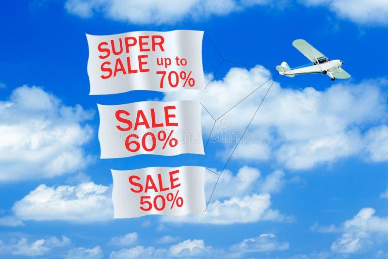 Petit avion remorquant la bannière avec la légende de VENTE dans le ciel Avion avec des bannières image libre de droits