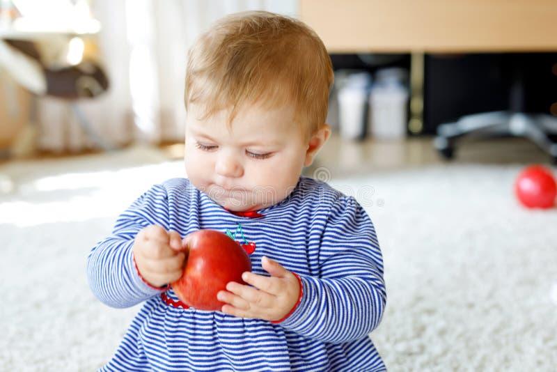 Petit bébé adorable mangeant la grande pomme rouge Vitamine et nourriture saine pour de petits enfants Verticale de bel enfant images libres de droits
