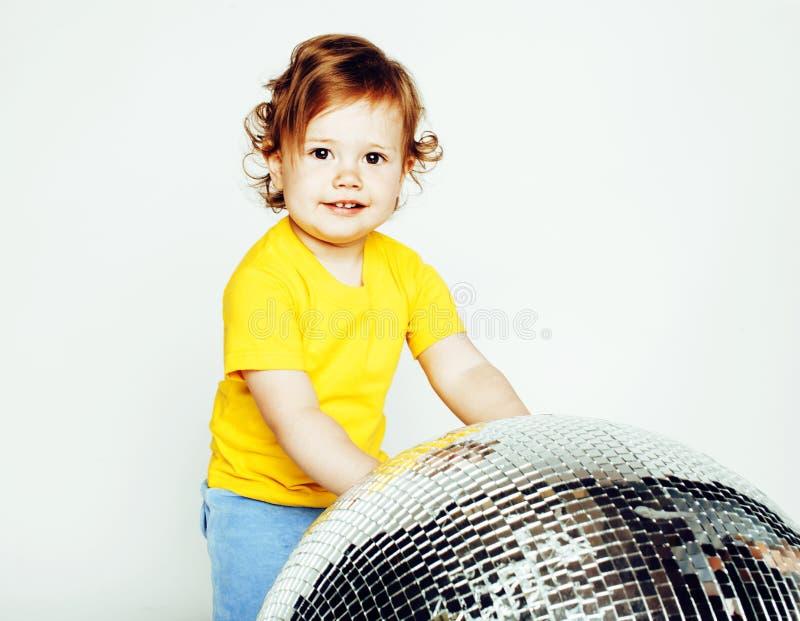 Petit bébé adorable mignon jugeant la boule de disco d'isolement sur la fin de blanc, vrai enfant en bas âge doux image libre de droits