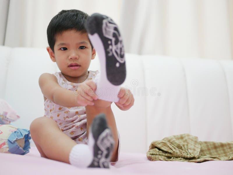 Petit bébé asiatique étant whiny tandis qu'elle essaye de mettre dessus des chaussettes images stock