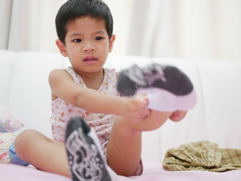 Petit bébé asiatique étant whiny tandis qu'elle essaye de mettre dessus des chaussettes photos libres de droits