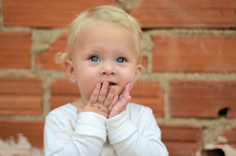 Petit bébé blond regardant avec le plaisir photos stock
