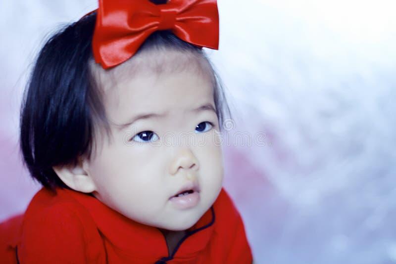 Petit bébé chinois innocent dans le cheongsam rouge photographie stock libre de droits