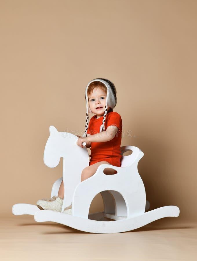 Petit bébé de sourire s'asseyant sur un cheval blanc, basculage en bois photographie stock