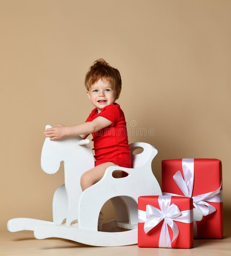 Petit bébé de sourire s'asseyant sur un cheval blanc, basculage en bois image libre de droits