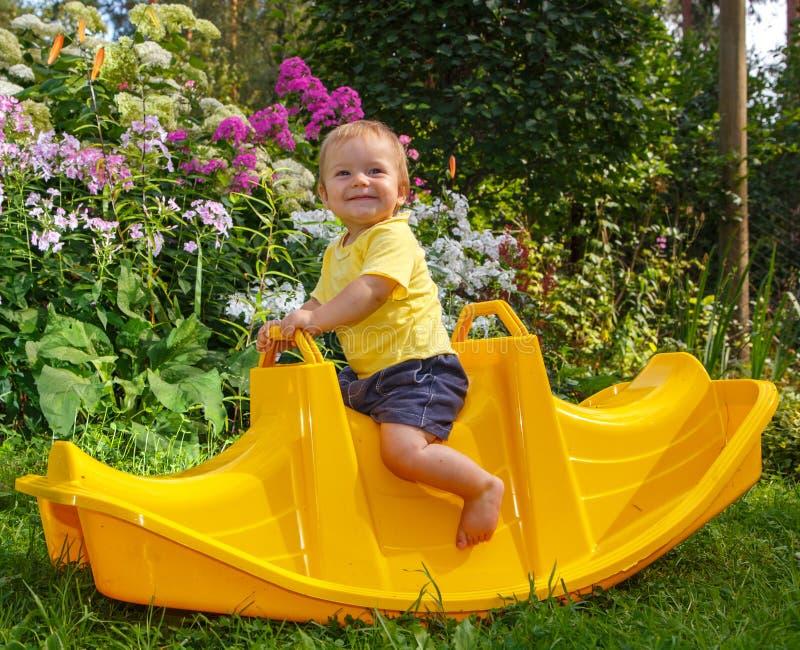 Petit bébé drôle sur son oscillation préférée photographie stock