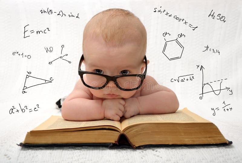 Petit bébé en verres avec des eauations autour photographie stock