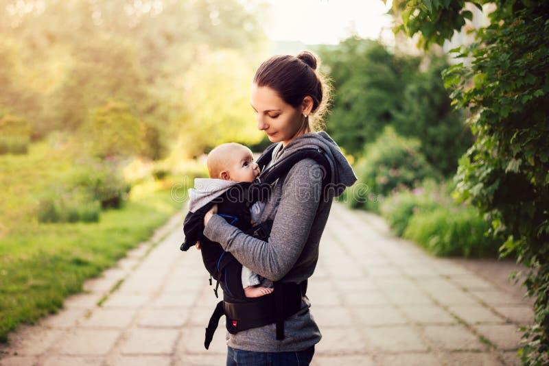 Petit bébé et sa mère marchant dehors pendant le coucher du soleil M images libres de droits