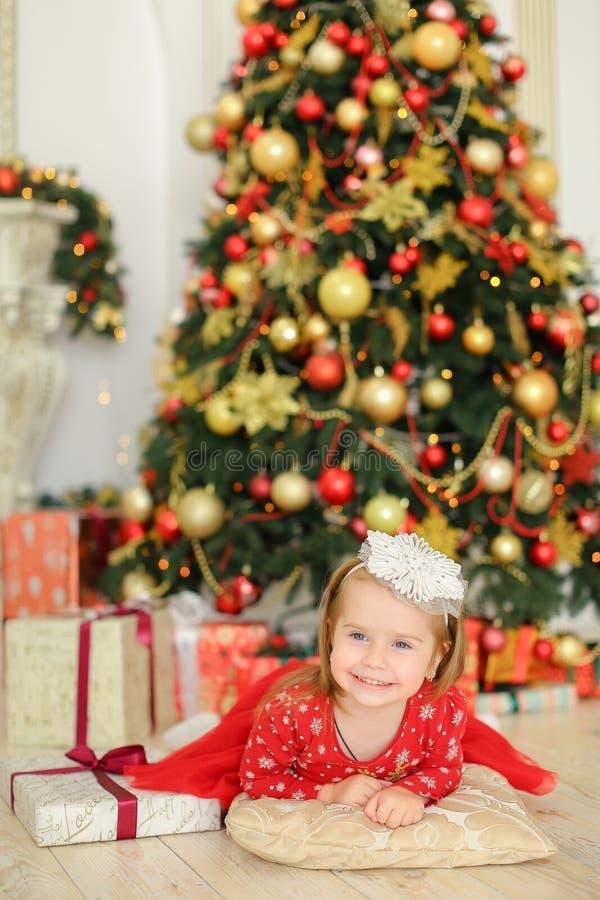 Petit bébé féminin caucasien se trouvant sur le plancher près de l'arbre de Noël et des présents mignons photos libres de droits