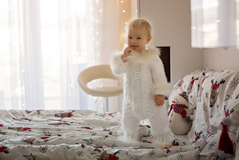 Petit bébé garçon adorable dans la combinaison tricotée à la main, mangeant des biscuits photos libres de droits